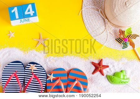 June 14th. Image of june 14 calendar on yellow sandy background with summer beach, traveler outfit and accessories. Summertime concept.