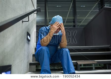 Tensed male surgeon sitting with hands on forehead on staircase in hospital