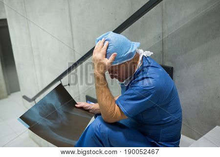 Tensed male surgeon examine x-ray on staircase in hospital