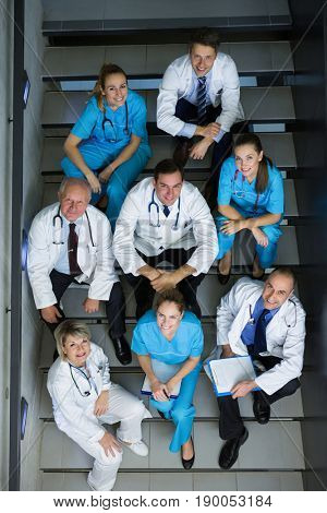 High angle view of doctors and surgeons sitting on staircase in hospital