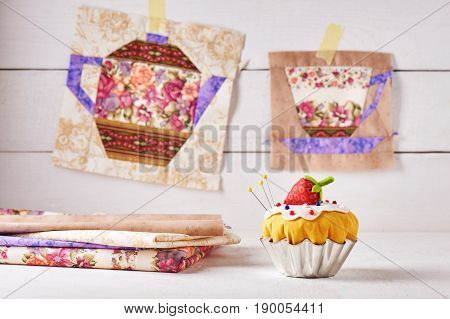 The pin cushion like a cupcake with strawberry and patchwork blocks of the cup and the teapot with a pattern of flowers hanging on wall