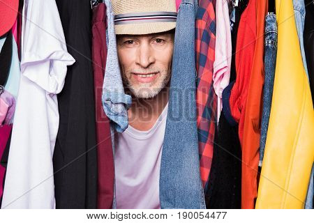Stylish Senior Man Wearing Hat And Standing With Diferent Clothes On Hangers And Looking At Camera