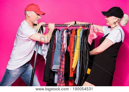 Happy Stylish Senior Couple Pulling Wardrobe With Diferent Clothes On Hangers Isolated On Pink