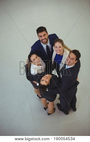 Portrait of businesspeople forming huddle in office