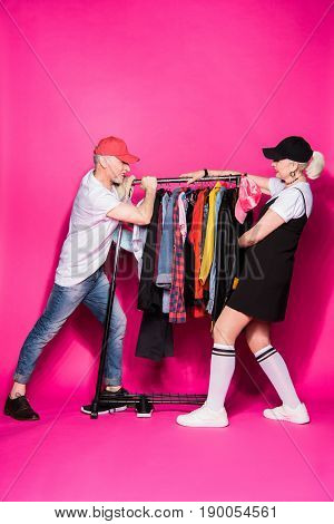 Stylish Senior Couple Pulling Wardrobe With Diferent Clothes On Hangers Isolated On Pink, Relationsh