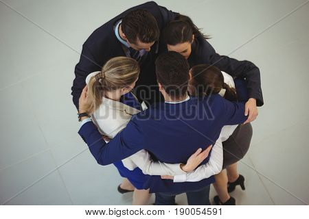 Businesspeople forming huddle in office
