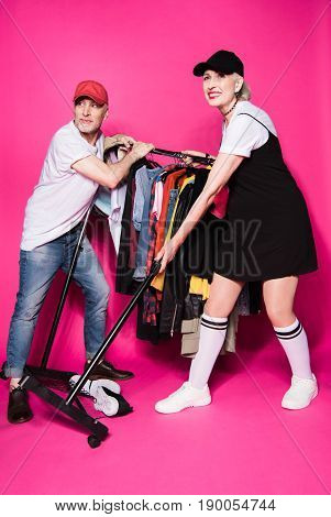 Stylish Senior Couple Holding Wardrobe With Diferent Clothes On Hangers Isolated On Pink