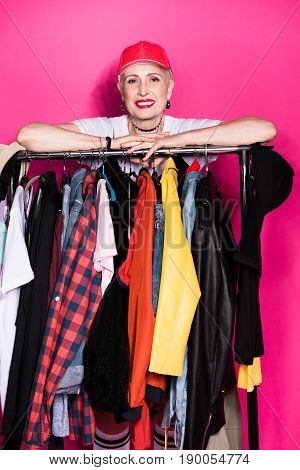 Smiling Senior Woman Standing Behind Diferent Clothes On Hangers Isolated On Pink