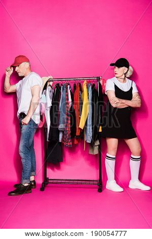 Stylish Senior Couple Standing With Diferent Clothes On Hangers Isolated On Pink, Relationship Diffi