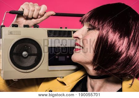 Profile Of Smiling Stylish Senior Woman Holding Tape Recorder Isolated On Pink