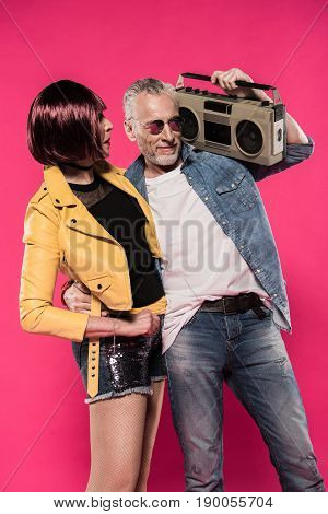 senior man with tape recorder on shoulder hugging woman isolated on pink