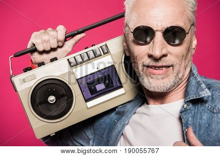 portrait of senior man holding tape recorder isolated on pink