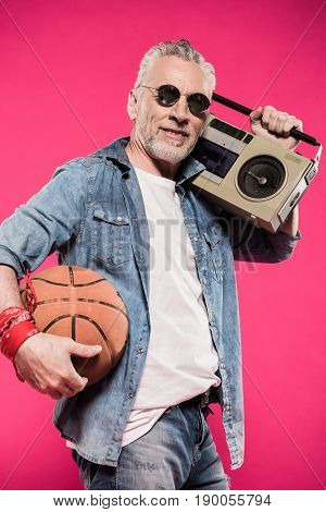 stylish man holding basketball ball and tape recorder isolated on pink