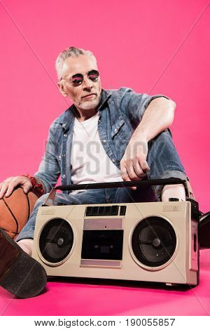 low angle view of man sitting near tape recorder and basketball ball isolated on pink