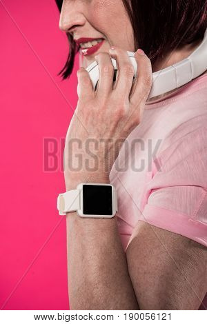 partial view of woman with smartwatch on wrist holding headphones