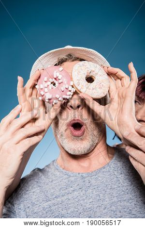 carefree elderly couple fooling around with sweet doughnuts