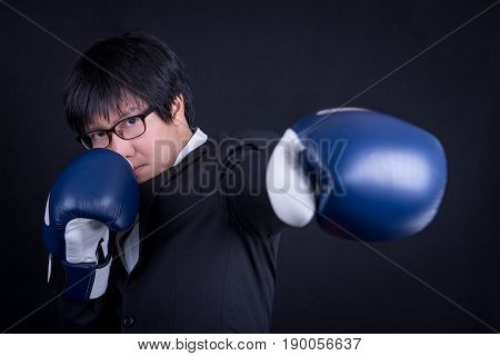 young asian business man wearing suit in boxing punching his left hand pose with black background studio. business man fight pose concept
