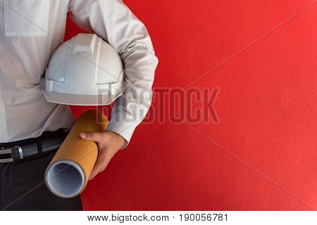 Engineer or Architect holding personal protective equipment safety helmet and architectural drawing in red background. Engineering Architecture and building construction management concepts