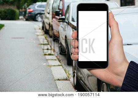 Man's hand with a smartphone on the background of cars parked on a city street. White screen, you can insert your own image or text here.