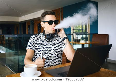 Young handsome hipster man with beard sitting in cafe with a cup of coffee, vaping and releases a cloud of vaporsitting. Working at laptop and having a little break.
