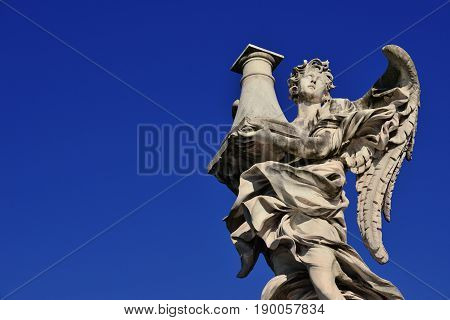 Angel statue holding the Column of Jesus Passion looks at the Heaven on Sant'Angelo Bridge in Rome (with blue sky and copy space)