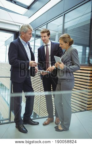 Businesspeople discussing over electronic devices in the passageway at officeoffice, workplace, passageway, profession, professional, executive, coworker, colleague, business, businesspeople,