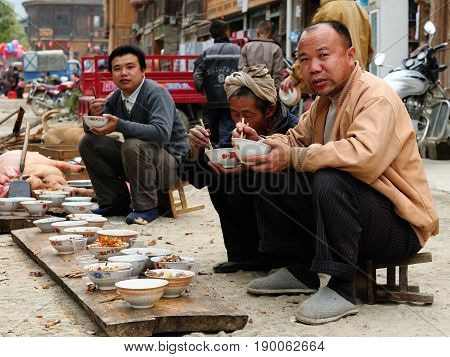 ZHAOXING CHINA - 11 NOVEMBER 2010: Residents of the Zhaoxing is a pretty Dong minority town eating on the High Street on the shared meal