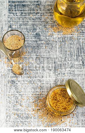 A jar with cooked mustard, a small glass with mustard seeds and a glass jug with mustard oil on a gray wooden background.