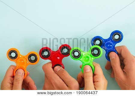 trendy fidget spinners - styled flat lay scene with hands holding generic design spinners