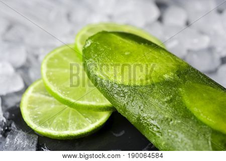 closeup of a homemade mojito ice pop made with natural lime juice, rum, mint and lime slices, on a natural slate tray surrounded by ice