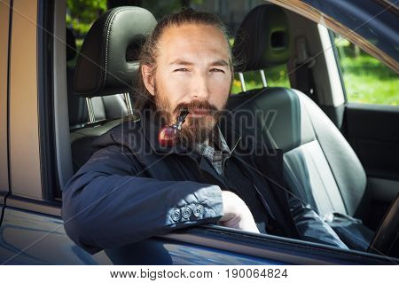 Asian Man Smoking Pipe. Driver Of Modern Car