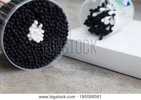 Cotton swabs folded slide black and white plastic sticks in plastic box