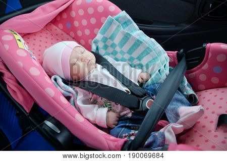 Newborn sleeping in car seat.Safety concept. Infant baby girl. secure driving with children. Baby care lifestyle. Cute baby sleeping in car.
