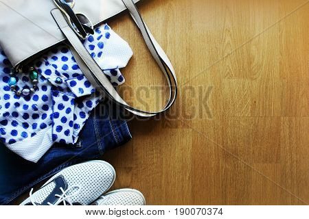 Collection of women's clothes. Jeans, shoes, bluose, glass Top view