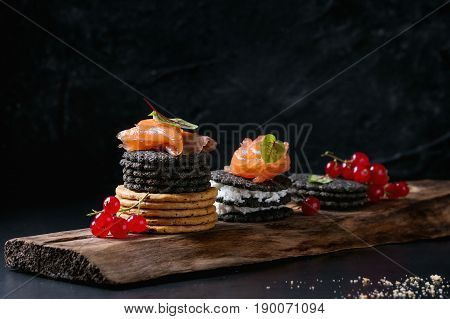 Stack of black charcoal and traditional crackers with smoked salmon, cream cheese, green salad and red currant berries on ood serving board over black metal background. Appetizer snack. Space for text