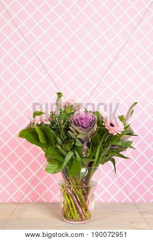 Colorful pink and purple bouquet in glass vase in interior