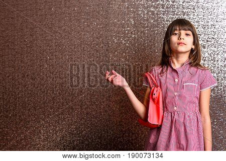 small pretty girl or cute fashionable child with long brunette hair and adorable face in checkered dress with female red leather bag on metallic silver background copy space