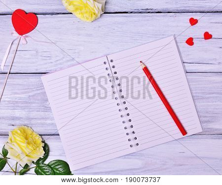 Open blank notebook and red wooden pencil top view