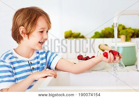 Happy Young Boy Washing The Armful Of Sweet Cherries Under Tap Water In The Kitchen