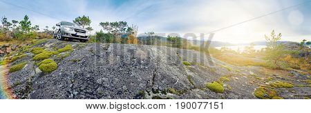 Panoramic view of norwegian rocks and distant fjord car parked on the top; lense flare.