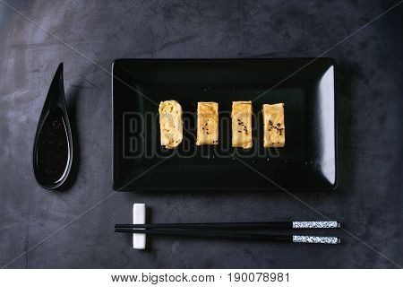 Japanese Rolled Omelette Tamagoyaki sliced with black seasame seeds and soy sauce, served in black square ceramic plate with chopsticks over dark metal background. Top view with space