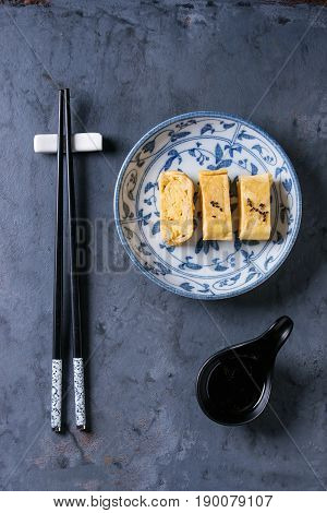 Japanese Rolled Omelet Tamagoyaki sliced with black seasame seeds and soy sauce, served in blue white ornate ceramic plate with chopsticks over blue gray metal background. Top view with space