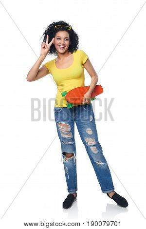 Full length happy mixed race african american - caucasian female in distressed jeans with skateboard gesturing V success hand sign