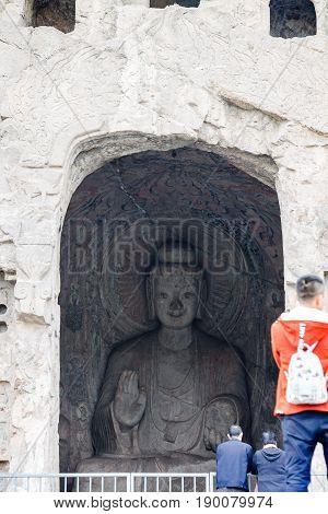 Visitors Near Sakyamuni Statue In Longmen Grottoes