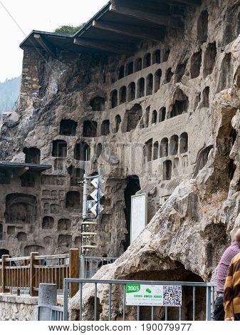 Tourists Near Caves In Longmen Grottoes