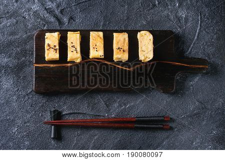 Japanese Rolled Omelet Tamagoyaki sliced with black seasame seeds and soy sauce, served on dark wooden serving board with chopsticks over black stone texture background. Top view with space