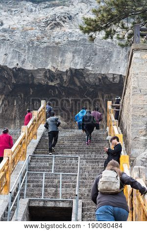 Tourists Climb To Cave In Longmen Grottoes