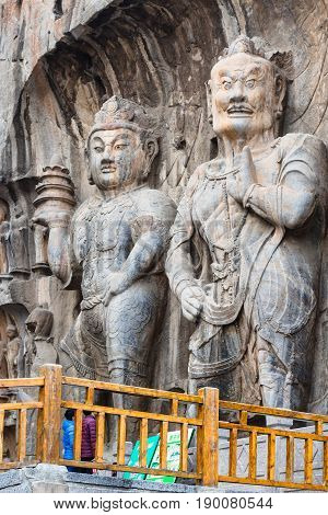 Visitors Near Buddhist Sculptures In Grotto