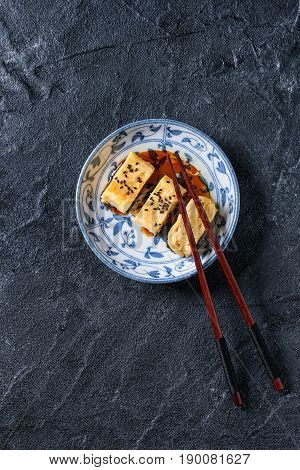 Japanese Rolled Omelet Tamagoyaki sliced with black sesame seeds and soy sauce, served in blue white ornate ceramic plate with chopsticks over black stone texture background. Top view with space