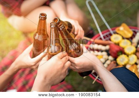 Group of friends clinking bottle of beer during camping outdoor party with barbecue in background